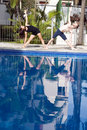 Free Couple Stretching Side At Poolside - Vertical Royalty Free Stock Image - 5615756