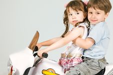 Adorable Boy And Little Girl Sitting On Toy Bike Stock Photography
