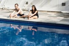 Free Couple Stretching Legs By Pool - Horizontal Stock Photo - 5616070