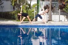 Free Couple Stretching At Poolside - Horizontal Royalty Free Stock Photography - 5616177