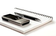 Mobile Phone Pen And Spiral Notepad On White Backg Royalty Free Stock Photos