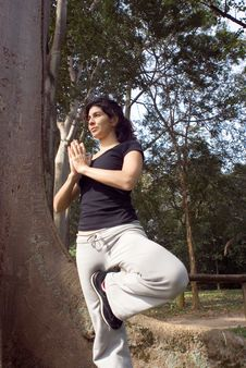 Woman In Yoga Pose Next To Tree - Vertical Royalty Free Stock Image