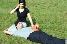 Man And Woman Sitting On Grass - Horizontal Royalty Free Stock Photos