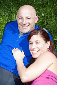 Free Couple Sitting On The Grass Laughing  - Vertical Royalty Free Stock Photos - 5626068