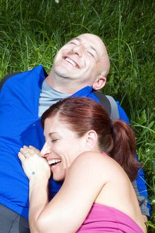 Free Couple Sitting On The Grass Laughing  - Vertical Stock Photography - 5640652
