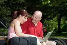 Couple On Park Bench With Laptop - Horizontal Stock Image