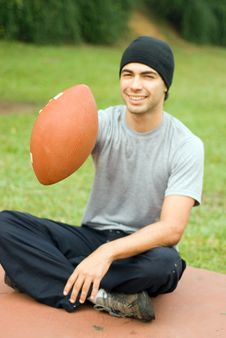 Man Sitting In Park Holding Football - Vertical Stock Photos