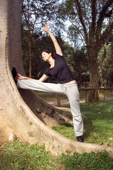 Free Woman Stretching Her Leg By A Tree - Vertical Stock Photography - 5641132