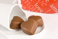 Three Heart Shaped Chocolates On A Cup And Saucer Stock Photos