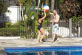 Free Man And Woman With Ball Next To Pool - Horizont Stock Photo - 5699000