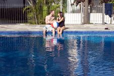Man And Woman Lounging Beside A Pool - Horizontal