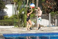 Man And Woman With Ball Next To Pool - Horizont Stock Photo