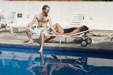 Man And Woman Lounging Beside A Pool - Horizontal Royalty Free Stock Photos