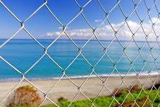 Free Beautiful Paradise Beach Seen Through Wires Of A Fence Royalty Free Stock Photos - 575718