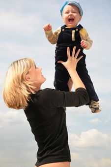 Mother Lifts Child On Hands Royalty Free Stock Image