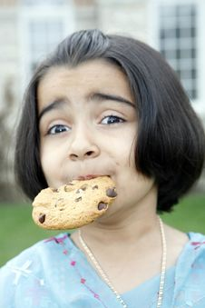 Little Girl Enjoying Cookie Royalty Free Stock Images