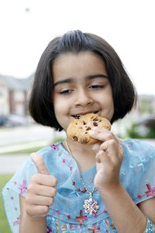 Little Girl Enjoying Cookie Stock Images