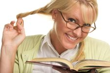 Female Plays With Ponytails & Reads A Book Royalty Free Stock Image