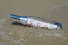 Message In A Bottle With SOS Signal Lying In Surf Royalty Free Stock Image