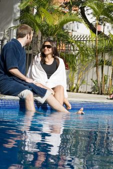 Man And Woman Lounging Beside A Pool - Vertical Royalty Free Stock Photos