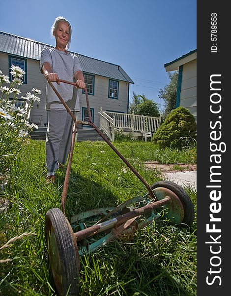 Germany Cologne Young Woman Mowing Lawn With Push Mower