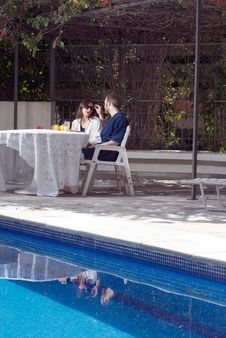 Free Couple Sitting At Table By Pool - Vertical Stock Images - 5792024