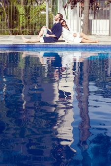 Free Man And Woman Lounging Beside A Pool - Vertical Stock Photography - 5792052
