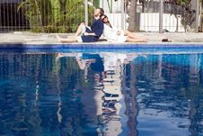 Man And Woman Lounging Beside A Pool - Horizontal Royalty Free Stock Images