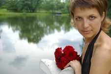 Attractive Young Woman With Red Flowers Stock Photo