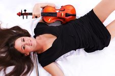 Beautiful Brunette Girl With Violin Laying On Bed Royalty Free Stock Photos