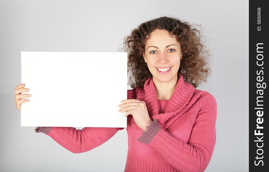 Young woman keeps white sheet of paper