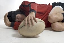 Man Laying On Floor Holding Rugby Ball - Horizonta
