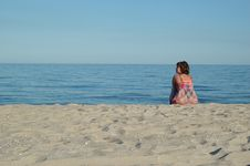 Young Woman Is Sitting On The Beach Stock Images