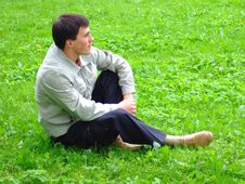 Thoughtful Young Man On A Grass. Royalty Free Stock Image