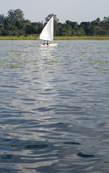 Couple Sailing Across Lake - Vertical Stock Image