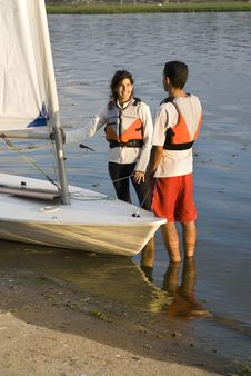 Couple Standing Next To Sailboat - Vertical Royalty Free Stock Image