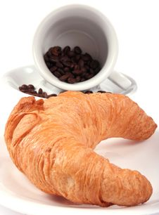 Croissant And Cup With Coffee Beans Stock Photos