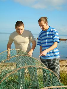 Two Men And Fishing Network. Stock Photography