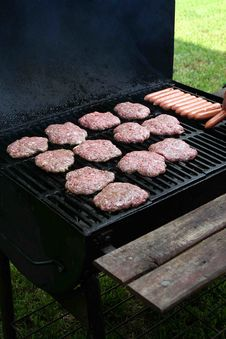 Grilling Hamburgers And Hotdogs Royalty Free Stock Photos