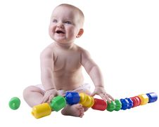 Free Baby Holding Large Plastic Beads In Lap. Stock Photos - 5931263