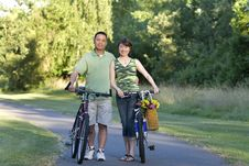 Couple Stands With Bicycles Smiling - Horizontcal Royalty Free Stock Image