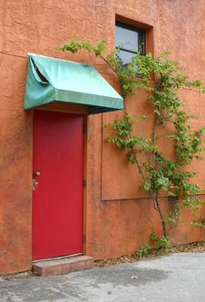 Red Door With Tattered Awning Royalty Free Stock Photo