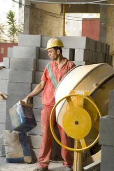 Worker Stands In Front Of Cement Mixer - Vertical Stock Photos