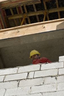 Worker Looks Over Cinder Block Wall - Vertical Royalty Free Stock Photos