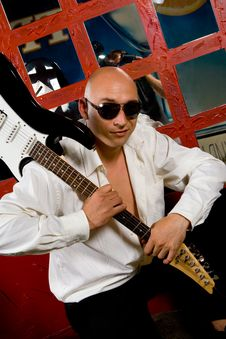 Man With Electric Guitar In Night Club Stock Photo