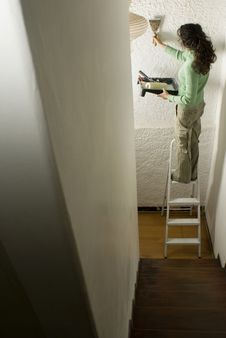 Free Woman Paints Wall While On Ladder - Vertical Stock Photo - 6063320