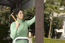 Free Smiling Woman Pounding Nail - Horizontal Stock Photo - 6063390