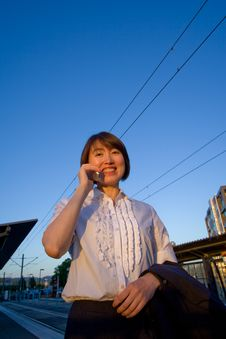 Woman On Cellphone Smiles At Camera - Vertical Stock Image
