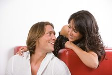 Smiling Young Couple Sitting On The Sofa Stock Image