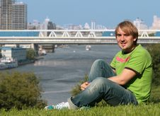 Happy Young Man Sitting On The Grass Stock Images